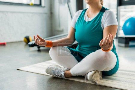 Photo pour Vue recadrée de plus femme de taille assise sur tapis de fitness avec jambes croisées - image libre de droit