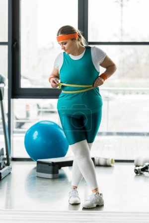 Photo for Overweight girl looking at measuring tape while measuring waist in gym - Royalty Free Image