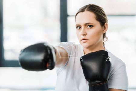 Photo for Selective focus of confident overweight girl practicing kickboxing - Royalty Free Image