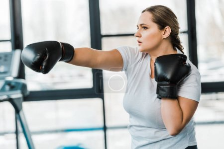 Photo for Serious overweight girl practicing kickboxing in gym - Royalty Free Image