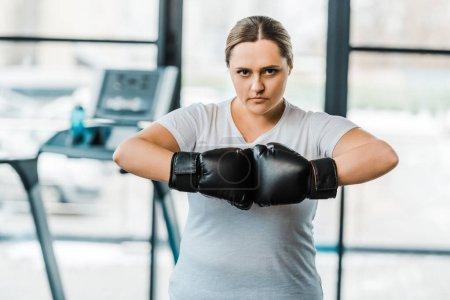 Photo pour Grave plus femme de taille avec des gants de boxe en regardant la caméra dans la salle de gym - image libre de droit