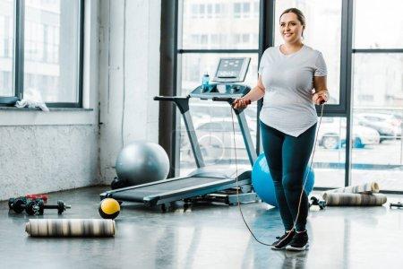 Photo pour Gai plus taille femme debout avec corde sautante dans la salle de gym - image libre de droit