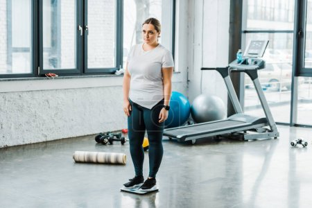 Photo for Sad overweight woman standing on scales in gym - Royalty Free Image