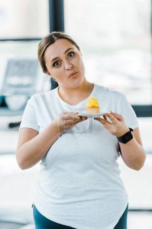 Photo pour Surpris femme en surpoids tenant délicieux cupcake dans la salle de gym - image libre de droit