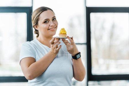 Photo pour Heureuse femme en surpoids tenant délicieux cupcake dans la salle de gym - image libre de droit