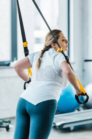 Photo for Overweight girl training arms with suspension straps in gym - Royalty Free Image