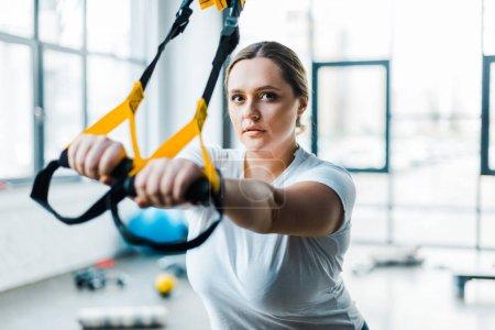 Photo pour Armoiries de formation confiant femme en surpoids avec sangles de suspension dans la salle de gym - image libre de droit