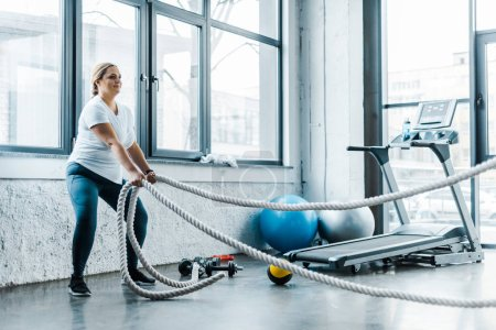 Photo for Overweight woman training with battle ropes in gym - Royalty Free Image