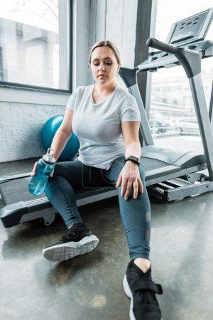 Photo pour Fatigué plus taille femme reposant sur tapis roulant et tenant bouteille avec de l'eau - image libre de droit