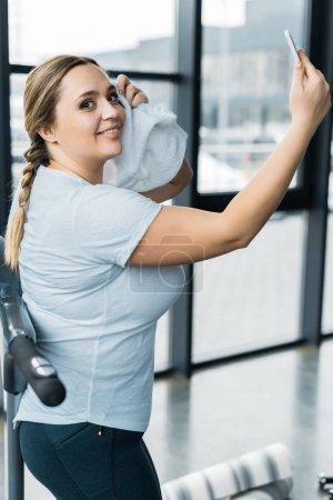 Photo pour Joyeuse fille en surpoids prenant selfie tout en tenant une serviette dans la salle de gym - image libre de droit