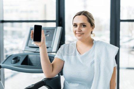 Photo pour Joyeuse fille en surpoids tenant smartphone avec écran blanc dans la salle de gym - image libre de droit