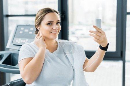 niña sonriente con sobrepeso sosteniendo el teléfono inteligente mientras escucha música en los auriculares
