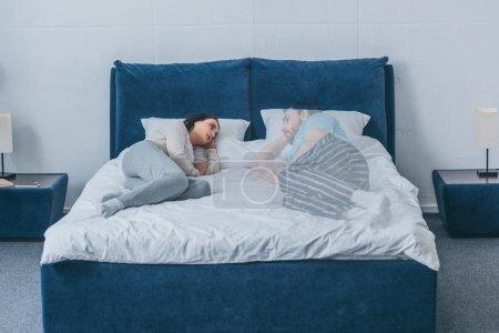 mujer deprimida acostada en la cama y mirando al fantasma del marido
