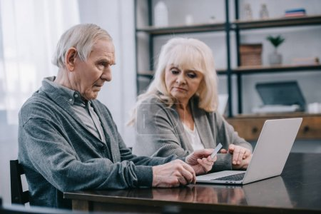 Photo for Senior couple sitting at table and using laptop at home - Royalty Free Image