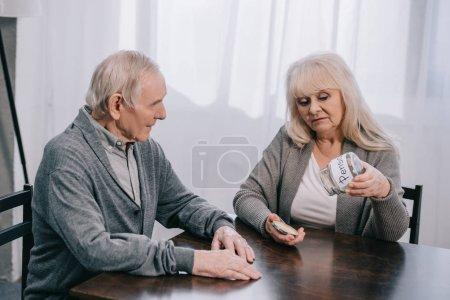 Photo pour Couple de personnes âgées triste assis à table et tenir le verre vide jar avec le lettrage «pension» - image libre de droit