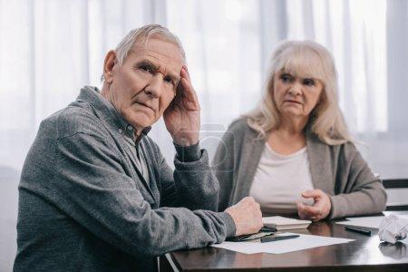 Photo pour Senior homme avec la main sur la tête, assis à table près de factures avec femme sur fond - image libre de droit