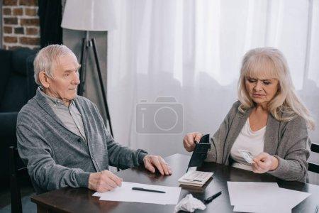 Seniorin hält Geldbörse und Geld bei Tisch mit Mann