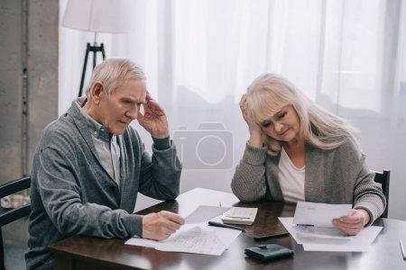 Gestresstes älteres Ehepaar mit händchenhaltenden Köpfen sitzt am Tisch und betrachtet Banknoten