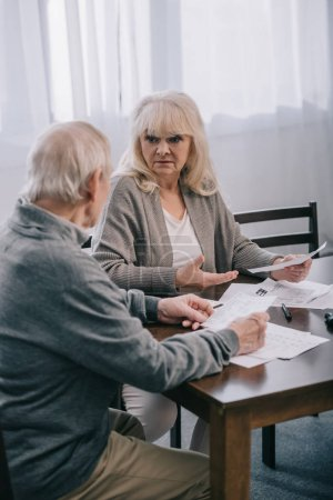 Photo for Surprised senior couple in casual clothes sitting at table and holding bills - Royalty Free Image
