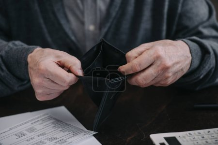 Photo for Cropped view of senior man holding empty wallet - Royalty Free Image
