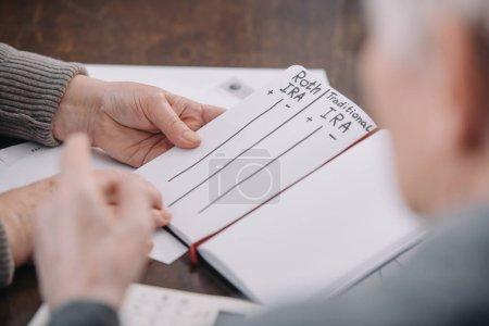 Photo pour Couple aîné tenant un carnet avec roth ira et mots ira traditionnels - image libre de droit