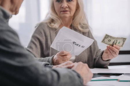 cropped view of senior couple holding envelope with 'roth ira' lettering and dollar banknote