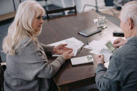 Photo pour Couple de personnes âgées assis à table avec la calculatrice, l'argent et formalités administratives - image libre de droit