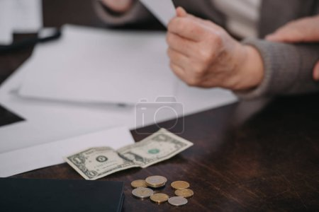Photo for Cropped view of senior woman sitting at table with paperwork, coins and banknote - Royalty Free Image