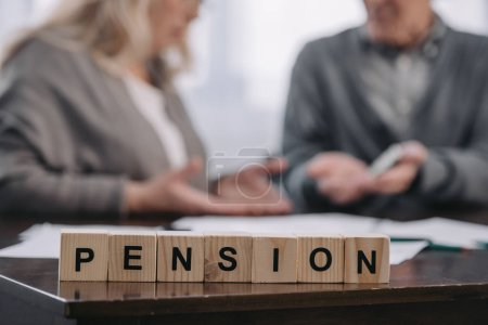 Photo for Selective focus of word 'pension' made of wooden blocks with senior couple on background - Royalty Free Image