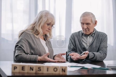Photo for Senior couple at table with word 'pension' made of wooden blocks on foreground - Royalty Free Image