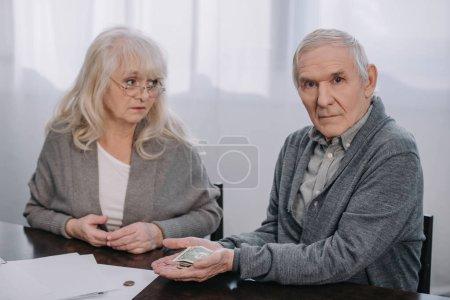 Photo pour Couple aîné en vêtements décontractés assis à table et tenant de l'argent dans les mains - image libre de droit