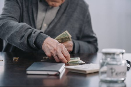 Photo for Partial view of senior man sitting at table and counting money at home - Royalty Free Image