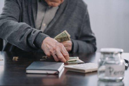 Photo pour Vue partielle du senior homme assis à table et compter l'argent à la maison - image libre de droit