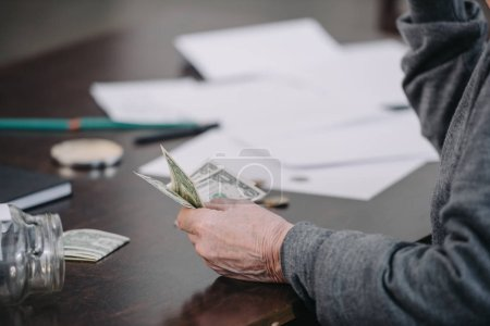 partial view of senior man sitting at table with paperwork and holding money