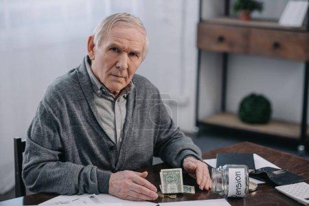 Photo pour Senior homme assis à table avec bocal argent, formalités administratives et le verre avec le lettrage «pension» - image libre de droit