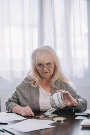 Photo pour Haute femme regardant la caméra et en maintenant le bocal en verre avec le mot «pension» en comptant l'argent - image libre de droit