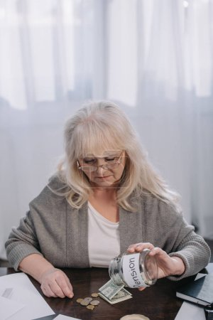 """Seniorin hält Glasgefäß mit """"Rente"""" -Wort, während sie zu Hause Geld zählt"""