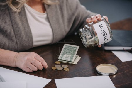 Photo for Cropped view of senior woman holding glass jar with 'pension' word while counting money at home - Royalty Free Image