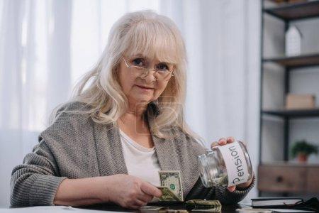 Photo pour Haute femme regardant la caméra, tenant le bocal en verre avec le mot «pension» et compter l'argent - image libre de droit