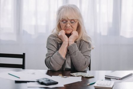 Photo for Tired senior woman sitting at table and propping head with hands while counting money at home - Royalty Free Image