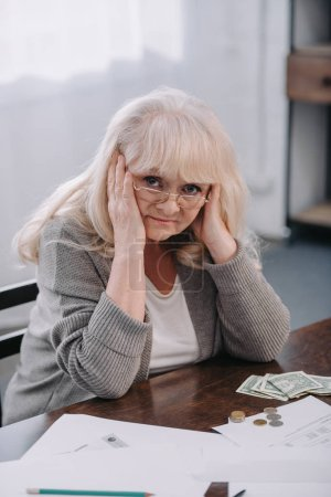 Photo for Senior woman with hands on head having headache and looking at camera while counting money at home - Royalty Free Image