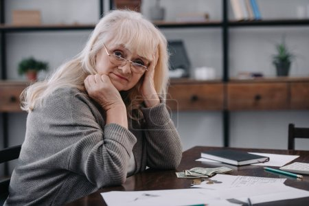 Photo for Tired senior woman sitting at table with money and paperwork while counting budget at home with copy space - Royalty Free Image