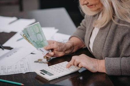 Photo for Cropped view of senior woman sitting at table, using calculator and counting money - Royalty Free Image
