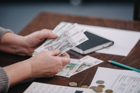 Photo for Close up of female pensioner counting money at home - Royalty Free Image