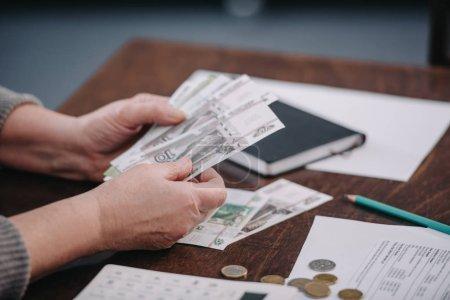 Photo pour Gros plan des pensionnées comptant l'argent à la maison - image libre de droit
