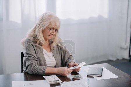 Photo pour Senior femme assise à la table avec de la paperasse et de compter l'argent - image libre de droit