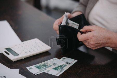 Photo pour Vue recadrée de la femme âgée tenant portefeuille avec de l'argent - image libre de droit