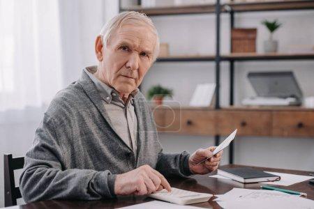 Senior sitzt mit Papierkram am Tisch, blickt in die Kamera und benutzt einen Taschenrechner, während er Geld zählt