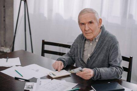 Photo pour Senior homme en vêtements décontractés assis à table avec de la paperasse et en utilisant la calculatrice tout en comptant l'argent - image libre de droit