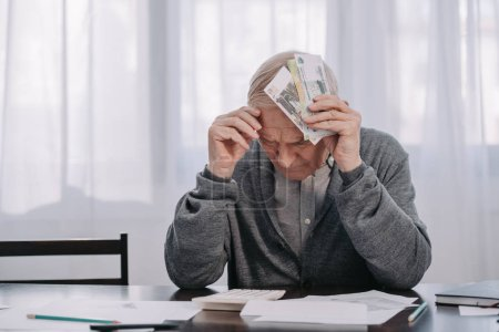 Photo for Stressed senior man sitting at table with paperwork and holding money at home - Royalty Free Image